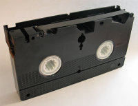 Bottom view of VHS cassette with magnetic tape exposed